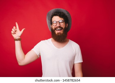 Photo of bearded guy in hat and glasses, pointing up at copy space over red background