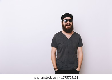 Photo of bearded man in hat and sunglasses with hands in pockets