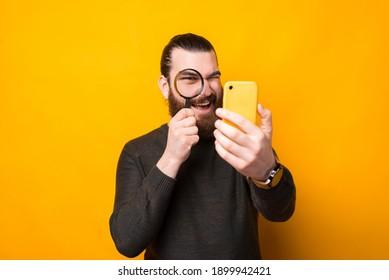 Foto von Bärenmenschen, die durch Lupe auf Smartphone schauen