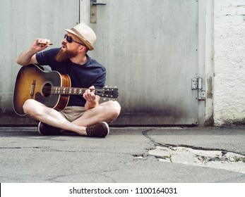 Photo of a bearded man playing acoustic guitar white smoking a cigar.