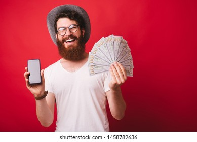 Photo of bearded man, wearing hat and glasses, showing at camrea his mobile and a lot of money