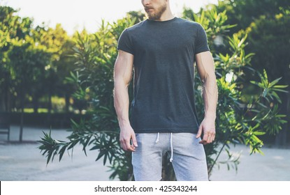 Photo Bearded Muscular Man Wearing Black Empty t-shirt and shorts in summer vacation. Relaxing time near the lake. Green City Garden Park Sunset Background. Front view. Horizontal Mockup