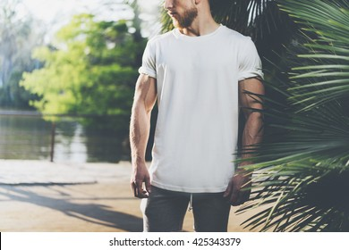 Photo Bearded Muscular Man Wearing White Blank t-shirt in summer time. Green City Garden, lake and palms Background,blurred. Horizontal Mockup.