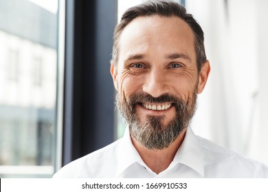 Photo of bearded pleased businessman in white shirt smiling and looking at camera while working in office