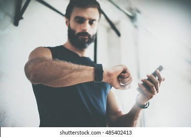 Photo Bearded Sportive Man After Workout Session Checks Fitness Results Smartphone.Adult Guy Wearing Sport Tracker Wristband Arm.Training hard inside gym.Horizontal bar background.Blurred