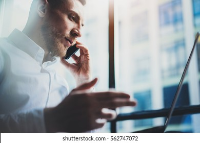 Photo bearded young businessman working on modern office. Man wearing white shirt and using contemporary smartphone. Panoramic windows background. Horizontal, film effect,blurred