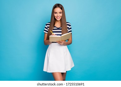 Photo of beautiful adorable lady hold diary copybook pen noting high school lecture good mood diligent student wear striped t-shirt white skirt isolated blue color background