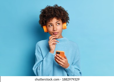 Photo of beautiful African American woman listens music with smartphone and headpones has thoughtful expression dressed in knitted jumpper isolated over blue background. Quarantine leisure concept