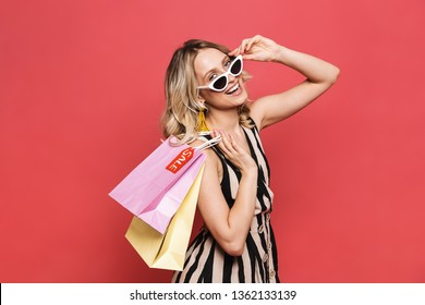 Photo of a beautiful amazing young woman posing isolated over red coral background holding shopping bags.
