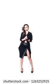 Photo of a beautiful attractive model wearing sexy black mini skirt with slit and rivets and black topcoat posing isolated on a white background