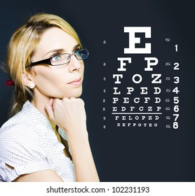 Photo Of A Beautiful Blonde Business Optician Or Optometrist Wearing Eye Wear Glasses Looking At Number And Letters On A Ophthalmology Chart To Check Eyesight