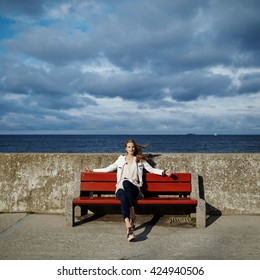 photo of beautiful blonde woman sitting on bench