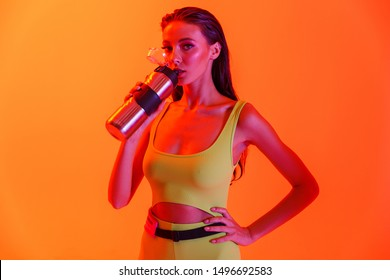 Photo of beautiful brunette woman wearing formfitting sportswear drinking water from metal bottle while doing workout isolated over orange neon wall