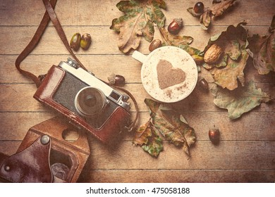 photo of the beautiful camera, cup of coffee and fallen leaves on the brown wooden background