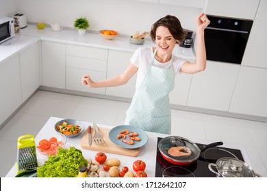 Photo of beautiful cheerful housewife lady peel boiled shrimps cooking and dancing excited prepared ingredients healthy food wear apron modern kitchen indoors