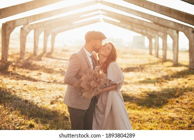 Photo of beautiful couple, groom kissing wife outdoor at sunset