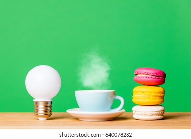 photo of beautiful cup of fresh coffee, bulb and colorful macaroons on the wonderful green studio wall background