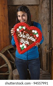 Photo of a beautiful female excited to eat her giant heart-shaped gingerbread cookie with Ich Liebe Dich written across.