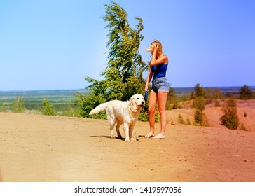 Photo of a beautiful girl with a dog on a big hill in summer
