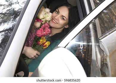 photo of Beautiful girl with flowers in the car