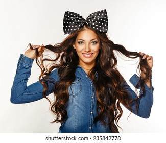 Photo of a beautiful girl with long hair and a bow on her head. Girl playful and alluring smile.