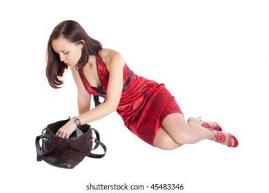 photo of beautiful girl in red dress looking for something in here handbag. Isolation on the white