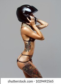 Photo of a beautiful girl in a swimsuit with a sports figure and hipster tattoos on a white background.