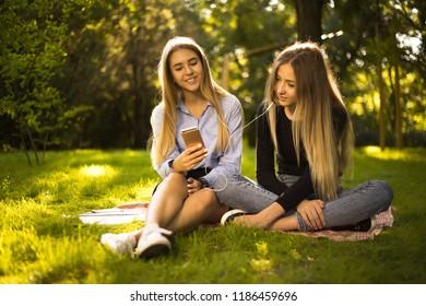 Photo of beautiful happy cheerful smiling girls sisters students sitting in the park outdoors on grass using mobile phone listening music with earphones.