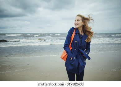 photo of beautiful happy girl on the windy coast