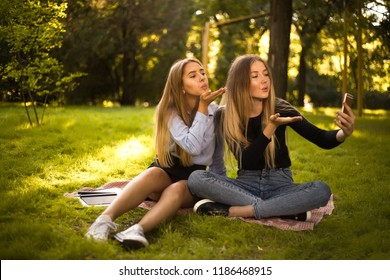 Photo of beautiful happy girls sisters students sitting in the park outdoors on grass have a rest take a selfie by mobile phone blowing kisses.
