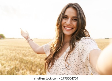 Photo of beautiful happy woman in stylish dress smiling while taking selfie photo on wheat field