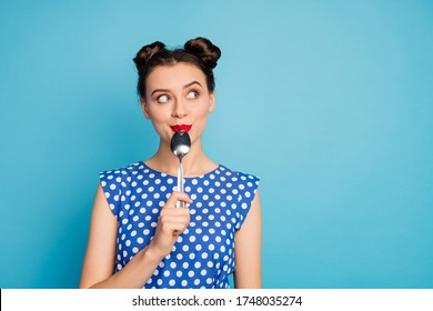 Photo of beautiful lady holding metal spoon in mouth look up empty space dreaming about tasty food wear dotted blouse shirt white isolated blue color background