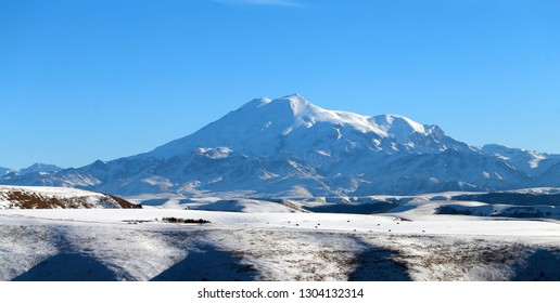 Photo of the beautiful landscape of snowy blue Elbrus in the distance in the North Caucasus