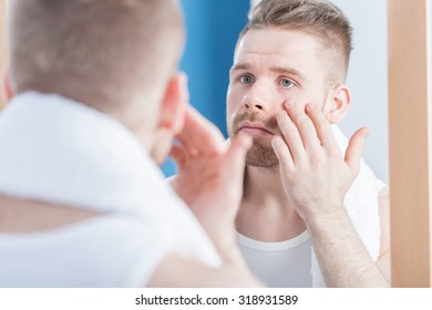 Photo of beautiful male narcissus examining his complexion