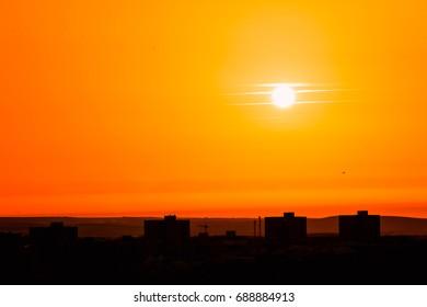 Photo of beautiful orange sunset on the city of Badajoz, silhouette city in sunrise on seashore, peaceful landscape, sun down on town on warm weather,  heat concept