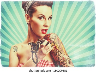 Photo of beautiful pin-up girl with tattoos and tattoo machine tattooing herself and looking at the camera. Retro styled imagery, toned image, grungy, noise added.