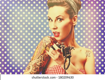 Photo of beautiful pin-up girl with tattoos, tattooing herself and looking at the camera against blue polka dot background. Retro styled imagery, grungy, toned image, noise added, vintage.
