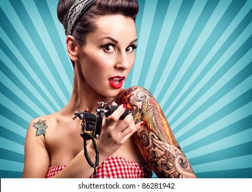 Photo of beautiful pin-up girl with tattoos and tattoo machine tattoing herself and looking at the camera
