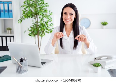 Photo of beautiful professional doc lady use modern technology notebook listen patient friendly smiling hold hands spectacles wear white lab coat sit chair office clinic indoors