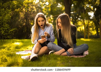 Photo of beautiful shocked surprised girls sisters students sitting in the park outdoors on grass using mobile phone listening music with earphones.
