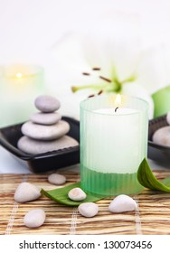 Photo of beautiful spa still life, spa stones, candle, white lily flower on bamboo table in spa-salon, aroma therapy, zen balance, bath items, beauty treatment, body care, dayspa, healthy lifestyle