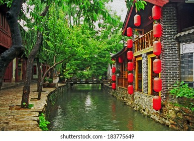 photo of beautiful street in lijiang, china, with a canal; old houses, trees and red lanterns stylized and filtered to look like an oil painting