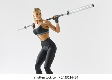 Photo of beautiful strong young woman with barbell and weight plates Fitness woman workout Fit young female athlete lifting heavy weights Caucasian female model performing barbell back squat