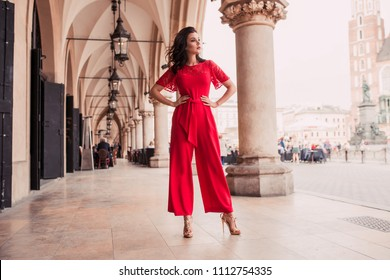 Photo of beautiful stylish brunette woman in the city ,wearing red jumpsuit. Fashion summer photo
