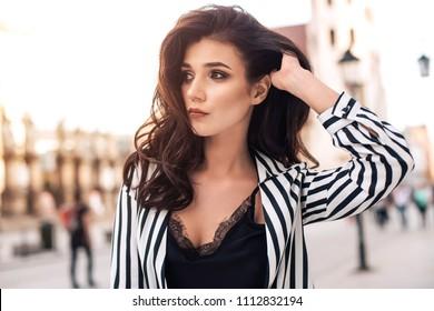 Photo of beautiful stylish brunette woman in the city ,wearing sunglasses, black and white stripes shirt. Fashion summer photo