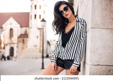 Photo of beautiful stylish brunette woman in the city ,wearing sunglasses, black and white stripes shirt, black shorts. Fashion summer photo