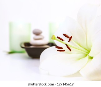 Photo of beautiful white lily flower, pebble stones, two candles, spa still life, dayspa, luxury beauty salon, hygiene items, bath objects, healthy lifestyle, organic cosmetics, resort concept