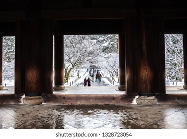 Photo of the beautiful winter landscape seen from one side of Nanzenji's massive Sanmon entrance gate, which extends over the treetops, taken in Kyoto City's Nanzenji Temple in Japan.