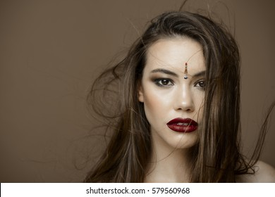 Photo of beautiful woman with magnificent hair. Dark red lipstick. Fashion photo. Over brown background.