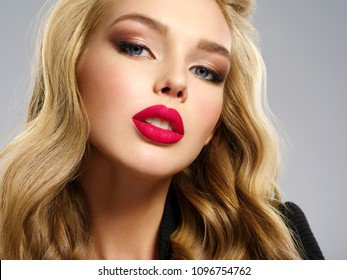 Photo of a beautiful young blond girl with sexy red lips. Closeup attractive sensual face of white woman with long hair. Smoky eye makeup